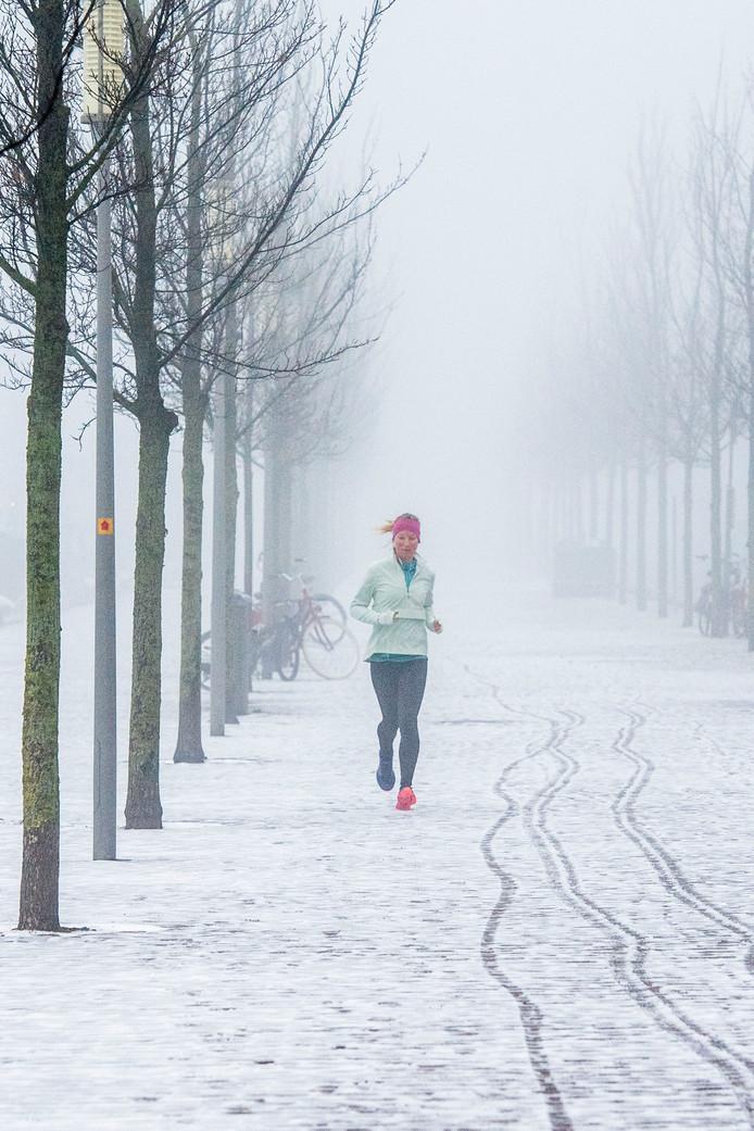 Rennen in de sneeuw in de Rotterdamse wijk Katendrecht.