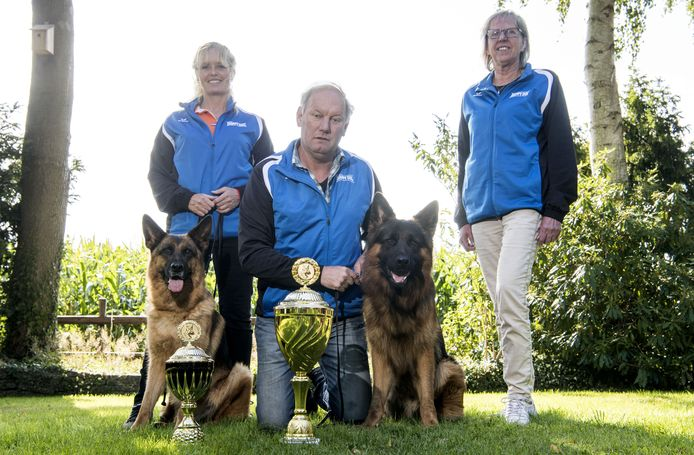 Jan Lentfert (midden) met hond Quote (rechts) en zijn vrouw Joke (rechts). En links trainster Ilona Sanders met moederhond Häsel.