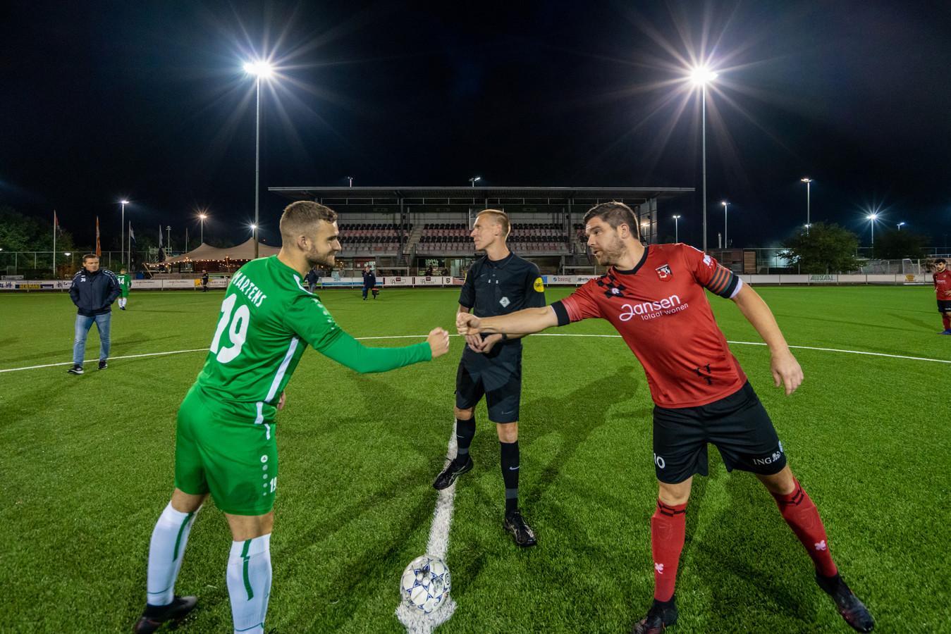 MASV trapt het verbrokkelde voetbalseizoen 2020-21 af als eersteklasser in Bemmel, na weken uitstel op een donderdagavond. Links aanvoerder Wesley Martens, rechts die van SC Bemmel: Ricky Houterman. Op de achtergrond: lege tribunes.