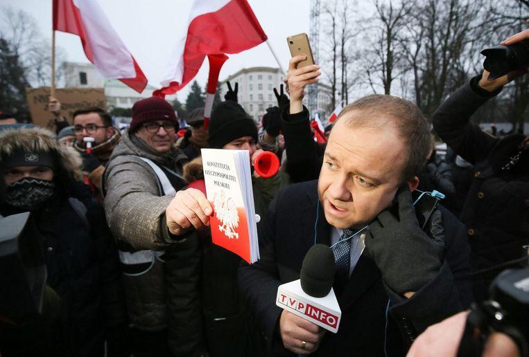 Demonstranten geven het Poolse wetboek aan een verslaggever van de zender TVP. Beeld EPA