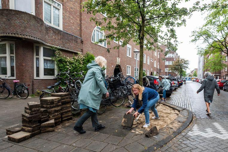 Buurtbewoners breken een stuk van de stoep open om er een bloementuin van te maken.  Beeld Hollandse Hoogte
