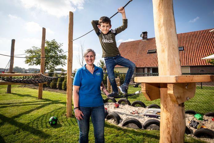Directeur Gea Wissink van kinderopvang De Drie Biggetjes met een van de vele kinderen die opgevangen worden op de landelijke locatie in Hertme.