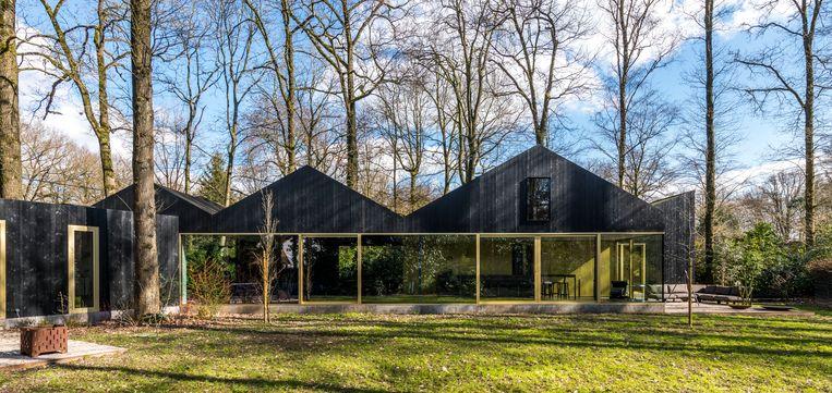 Ook in de gevel beperkten de BASIL-architecten  zich tot het palet van zwart en goud, met geoliede planken en geanodiseerde raamkaders.   Beeld Luc Roymans