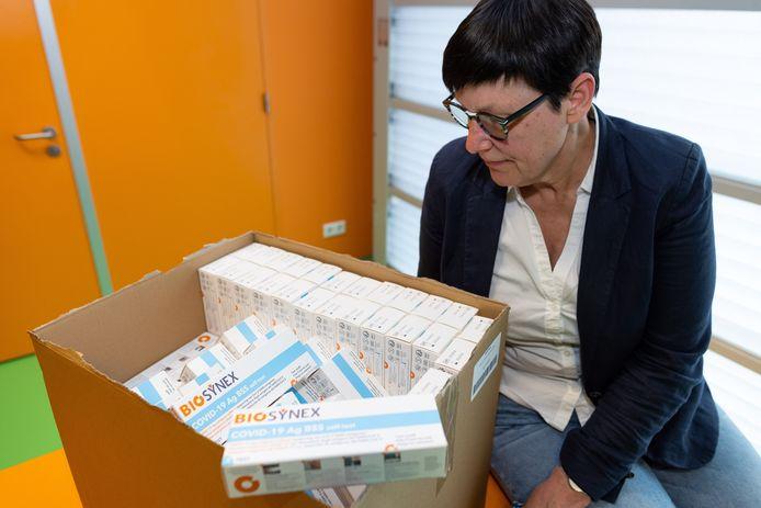 Directeur Nicolle Sommer van de Walewycmavo bij een aangebroken doos met corona-zelftests.