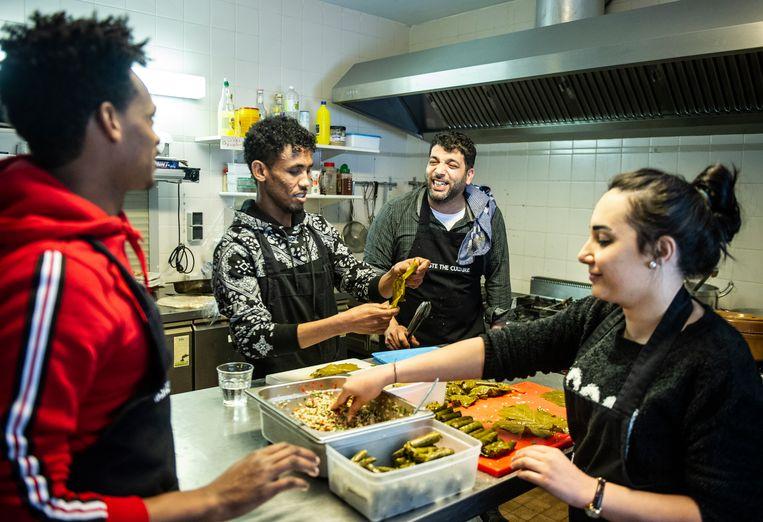 De Syrische chef-kok Ayman Mezyan Momo (tweede van rechts) aan het werk met zijn collega's in Le Souk d'Orient. De hele ploeg volgt op maandag een horeca-opleiding. Beeld Koen Verheijden
