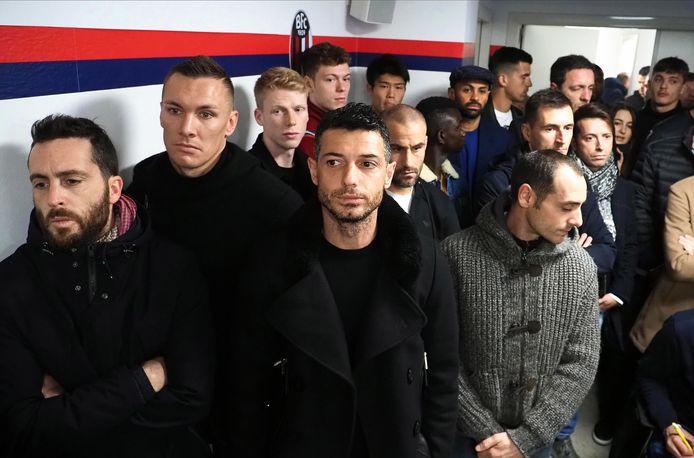 De spelersgroep van Bologna luistert naar zijn coach in het ziekenhuiszaaltje.