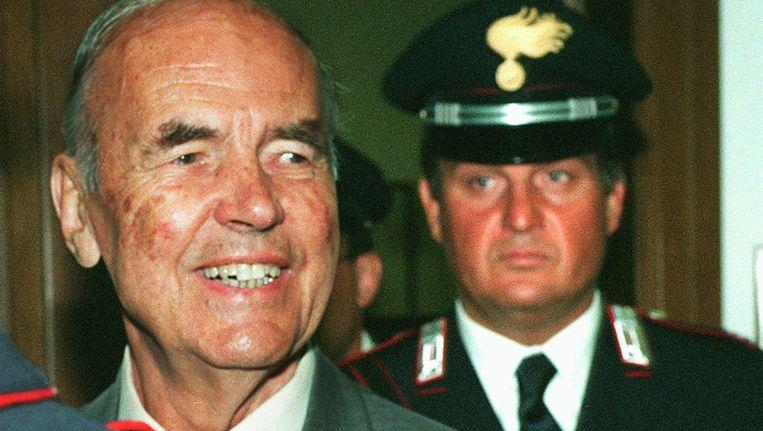 Erich Priebke, in juli 1996. Hij verlaat hier een militaire rechtbank in Rome. Op de achtergrond een Italiaanse agent. Beeld ap