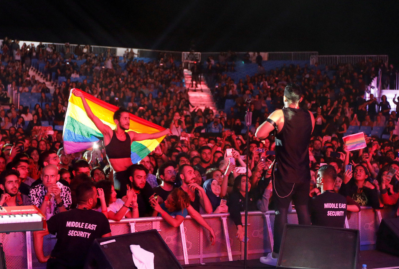 Een fan van Mashrou' Leila met regenboogvlag tijdens een concert in de Libanese stad Ehden op 12 augustus 2017.