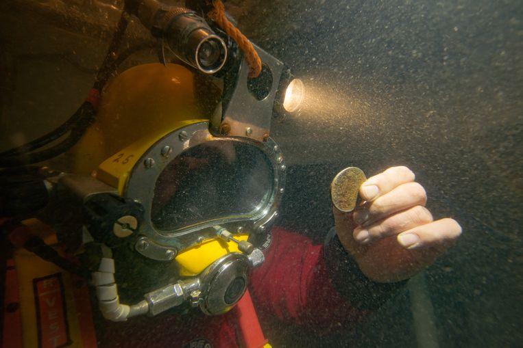 Maritiem archeoloog Martijn Manders met een zilveren munt uit het wrak van de Rooswijk. Beeld Rijksdienst voor het Cultureel Erfgoed - Michael Pitts