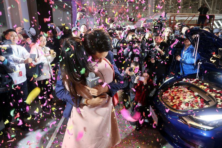Een Chinese Tesla-medewerker vulde zijn nieuwe auto met bloemen en deed een huwelijksaanzoek tijdens de leveringsceremonie. Beeld Reuters