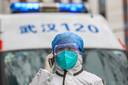 Een verpleger loopt naast een ambulance in Wuhan.