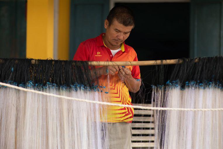 Hung repareert zijn netten voor de wind draait en hij weer het water op kan. Beeld REHAHN C