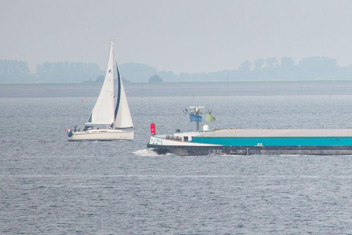 Een binnenvaartschip en een zeilboot passeren elkaar op de Oosterschelde.