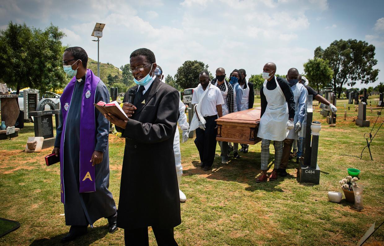 Onder een gebed van de predikant brengen dragers de kist naar de laatste rustplaats van de overledene.