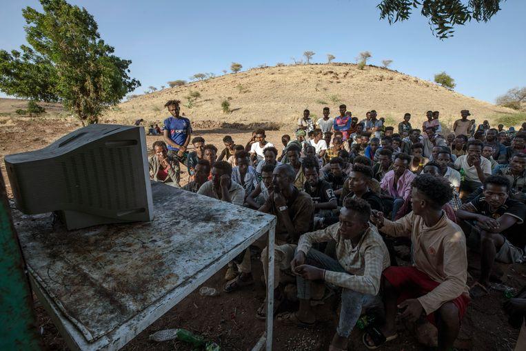 Ethiopische vluchtelingen kijken naar het nieuws op een televisie in een vluchtelingenkamp in Soedan. Beeld AP