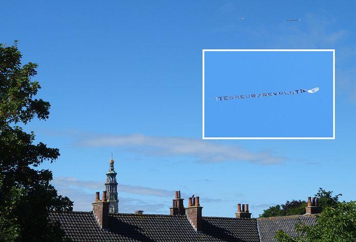 Het vliegtuigje boven het centrum van Middelburg. Inzet: vlag met de tekst terreur-revolutie.