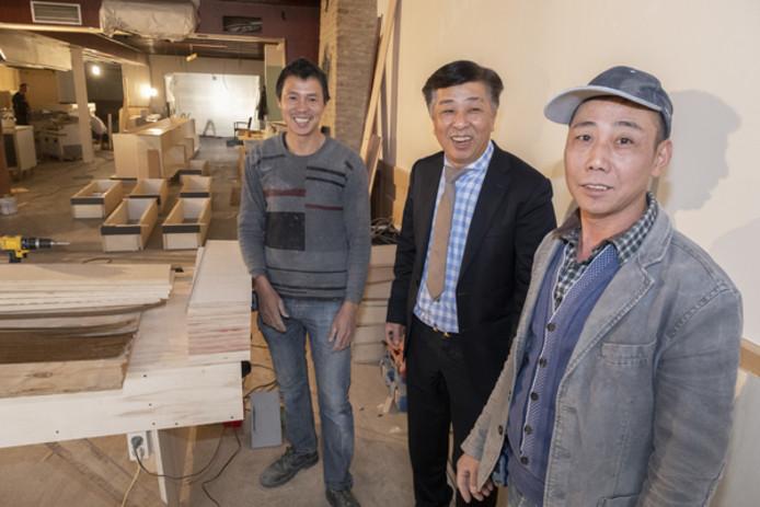 Shaosong Hu te midden van twee van de zestien bouwvakkers die Royal Palace verbouwen. Deze Chinese mannen zijn naar Renesse gehaald om speciale buffetkasten te maken.