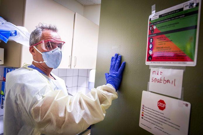 Een verpleegkundige in steriele kleding in de sluis voor een isolatiekamer in een ziekenhuis.