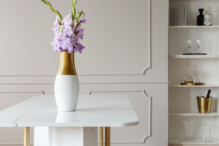 Lavender purple flowers in a golden vase on a white marble table in an elegant dining room interior with molding on beige walls Beeld Getty Images/iStockphoto