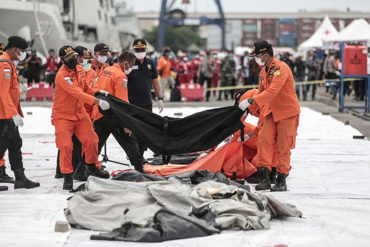 Hulpverleners leggen bodybags op een rij in de haven van Jakarta. Bij de ramp met een Boeing 737-500 van Sriwijaya Air kwamen 62 mensen om het leven. Beeld AFP
