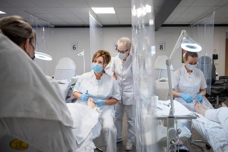 Marjan Korsten (links met blauw mondkapje) tijdens een praktijkdag van haar opleiding tot praktijkondersteuner podotherapie. Beeld Bram Petraeus