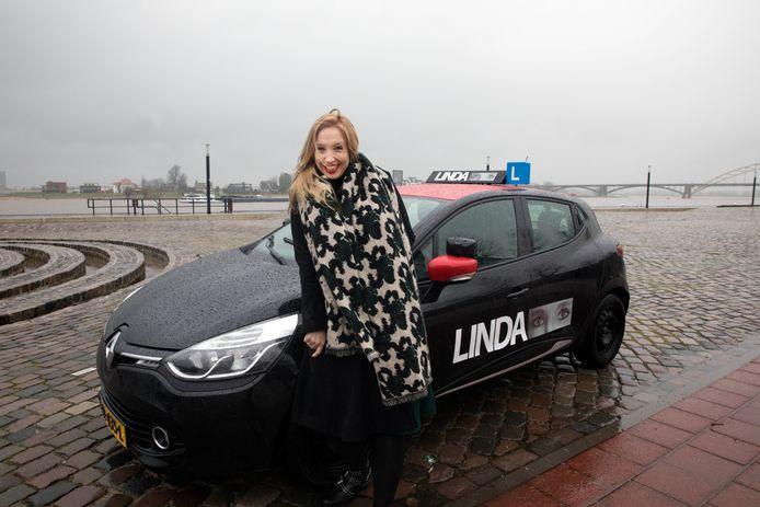 Linda Wilting bij de auto met het 'Linda-logo'.