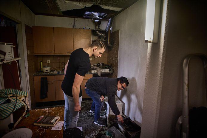 Bewoners Branko Nedeljkovic en Leon Castro bekijken de plek waar een brand heeft gewoed.