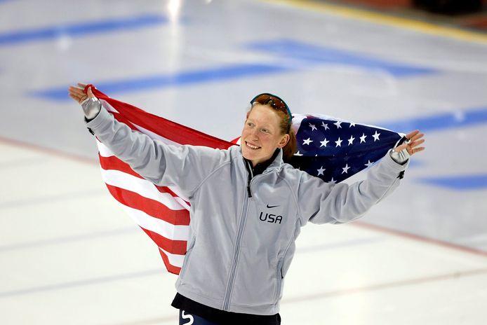Chris Witty viert haar olympische titel op de 1000 meter met de Amerikaanse vlag op het ijs.