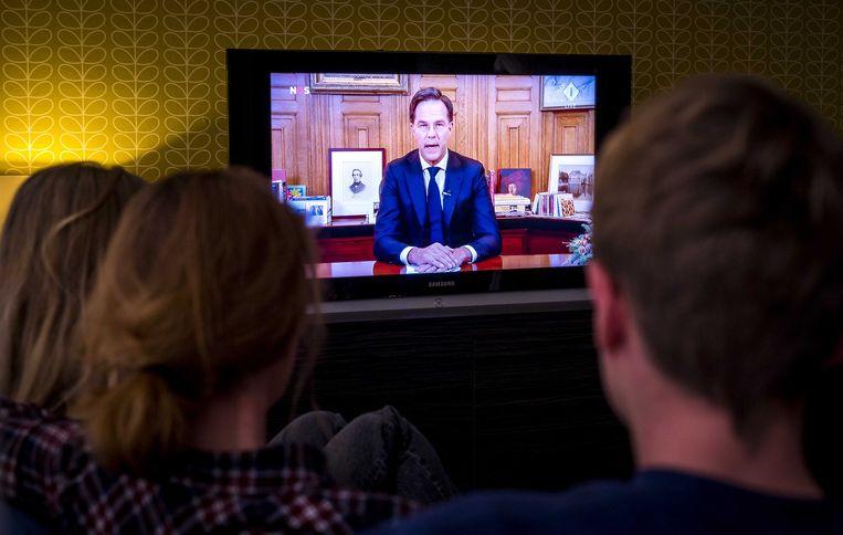 Een gezin met schoolgaande kinderen kijkt naar de toespraak van premier Mark Rutte over verscherping van de coronaregels. Beeld ANP