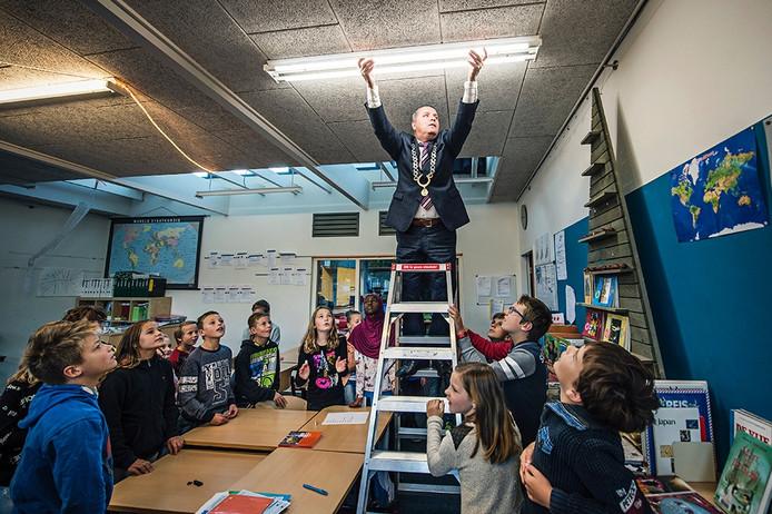 Burgemeester Marcel Delhez plaatst de eerste ledlamp in basisschool Het Stelleplankier in Colijnsplaat.
