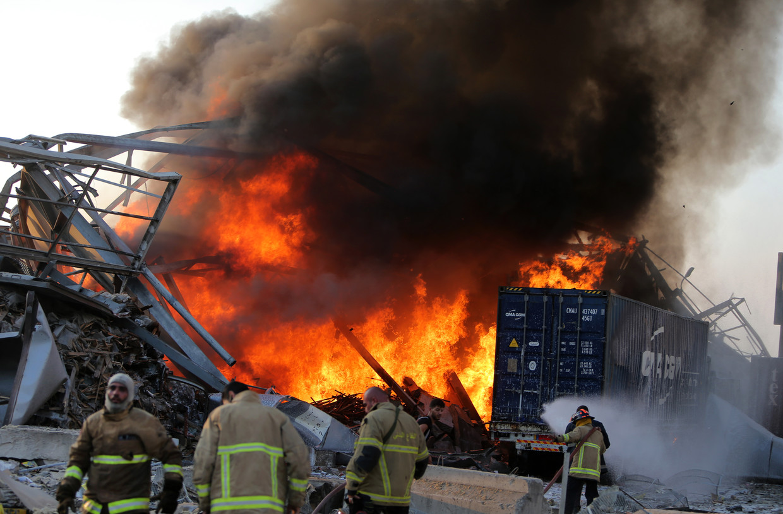 Brandweermannen proberen het vuur onder controle te krijgen na de explosie.