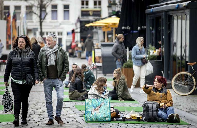 Mensen picknicken op een kleed op de Grote Markt in het centrum van Breda. Het is een ludieke protestactie van ruim 60 ondernemers tegen de coronamaatregelen. Beeld ANP