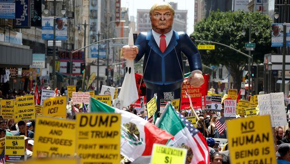 Een opblaasbare Donald Trump en tal van leuzen tijdens een protestmars in de straten van Los Angeles.