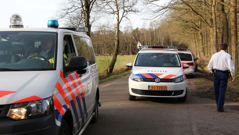 Boven en onder: Politieagenten doorzoeken de omgeving van de camping aan de Oude Buurserdijk waar het duo een gezin zou hebben gegijzeld. Beeld anp