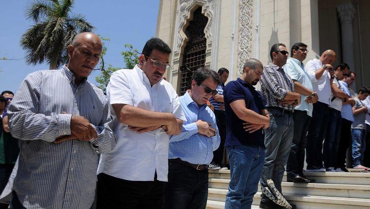 Familieleden en vrienden van slachtoffers houden een herdenking aan een moskee nabij de luchthaven van Caïro. Beeld epa