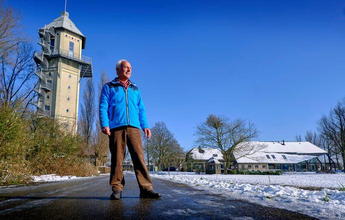Piet Bijl op de Kromme Zandweg in Dubbeldam met op de achtergrond links de Watertoren en rechts een oude verbouwde boerderij.