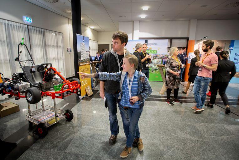 Bezoekers  van de techbeurs in het EXPO te Leeuwarden, kijkend naar een zelfsturende kart.  Beeld Herman Engbers