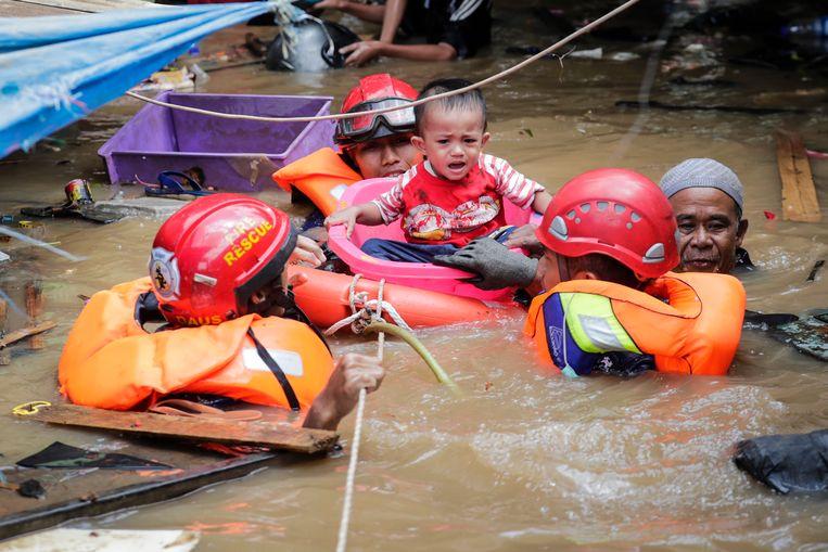 Reddingswerkers redden een jongetje in Jakarta. Beeld EPA