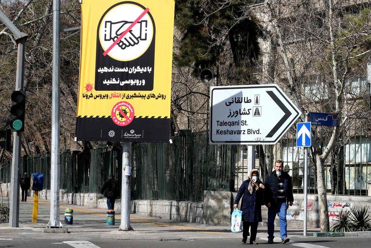 Iraniërs dragen mondkapjes en wandelen langs een poster die mensen waarschuwt geen handen te schudden om verspreiding van het coronavirus tegen te gaan.  Beeld AFP