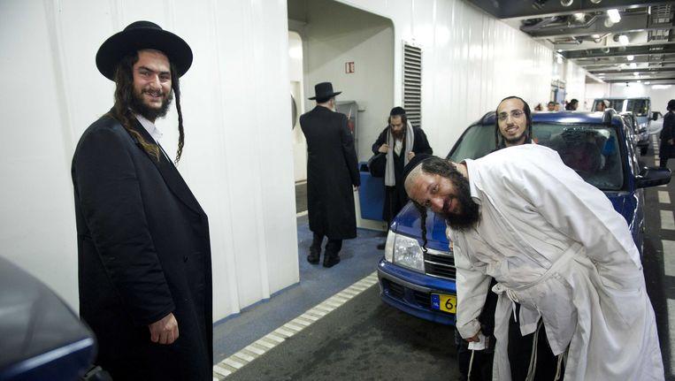 Volgelingen van Eliezer Berland schermen hun rabbijn af van de fotograaf, op de veerboot tussen Den Helder en Texel Beeld ANP