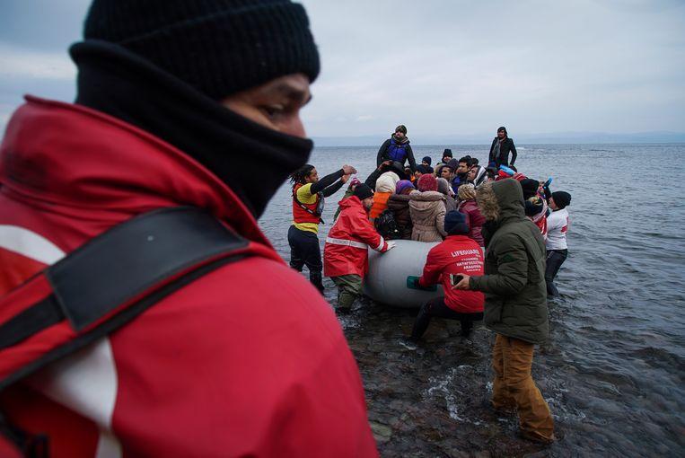 Medewerkers van het Griekse Rode Kruis en vrijwilligers helpen in januari 2016 Syrische vluchtelingen aan wal op Lesbos. Beeld AP