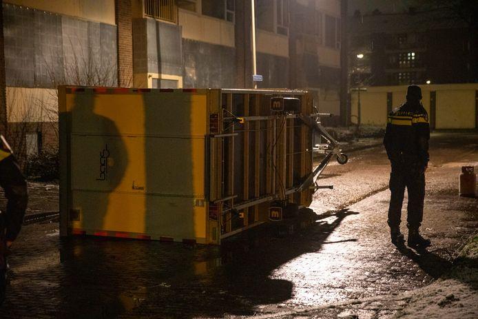 Een bouwkeet ligt op de kant in Bergen op Zoom. Ernaast staat de gasfles die uit de keet is gehaald.