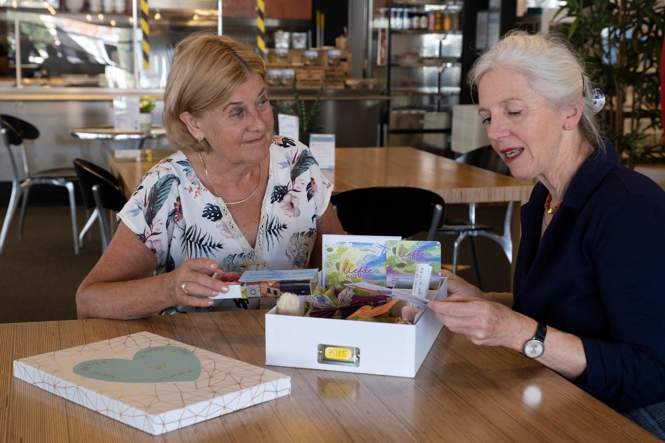Gerda van Leeuwen (l) en Anja Ganzeboom met een voorbeelddoos.