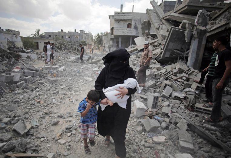 Een Palestijnse vrouw loopt in 2014 langs de puinhopen van gebouwen die zijn getroffen door Israëlische luchtaanvallen. Beeld AP