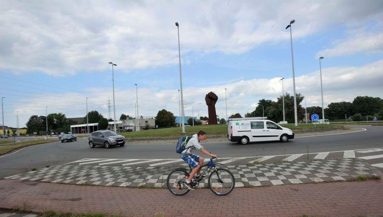 Een fietser deelt de rotonde met enkele wagens, zij het elk op hun rijbaan. Gevaarlijk wordt het wanneer die auto's de rotonde willen verlaten.