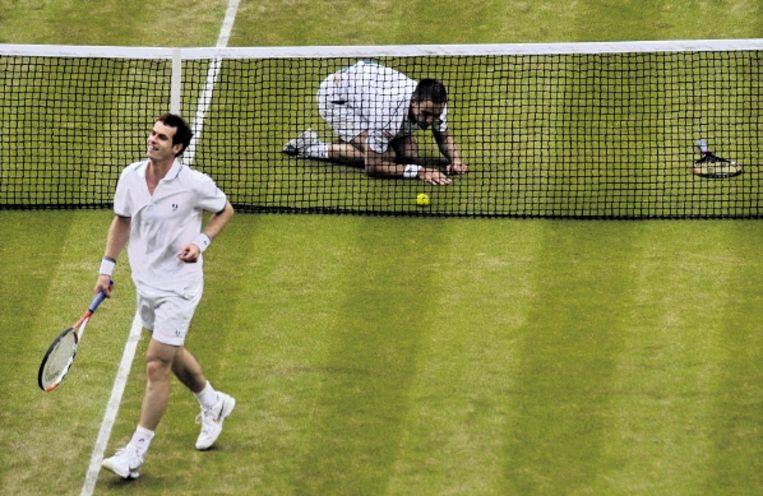 Murray loopt lachend weg terwijl zijn tegenstander Troicki vertwijfeld bij het net achterblijft. (FOTO AFP) Beeld