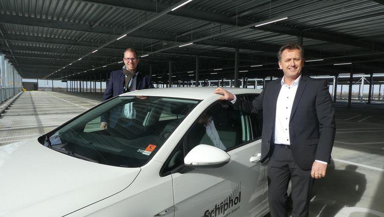 De projectmanagers achter het stuur: Niels van Dalen (Ballast Nedam Parking) en Henk de Pater (Schiphol). Maar eerst de gordel om. Beeld Hans van der Beek