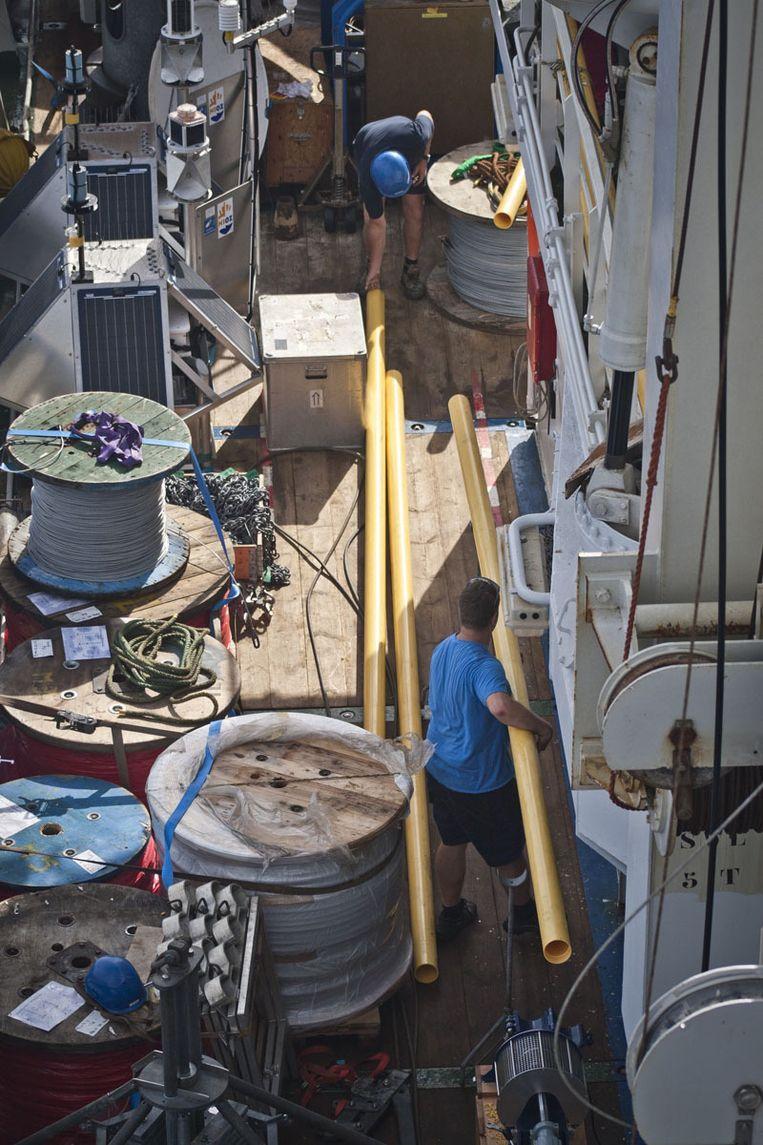 Het technische team klust op het dek aan de nieuwe cilinder. Beeld Ronald Veldhuizen