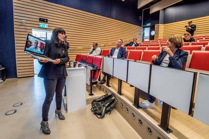 Op gepaste afstand krijgt burgemeester Van Bijsterveldt, onder het toeziend oog van CvB-voorzitter Tim van der Hagen, 'We/Visit-college' van Elif Özcan Vieira.