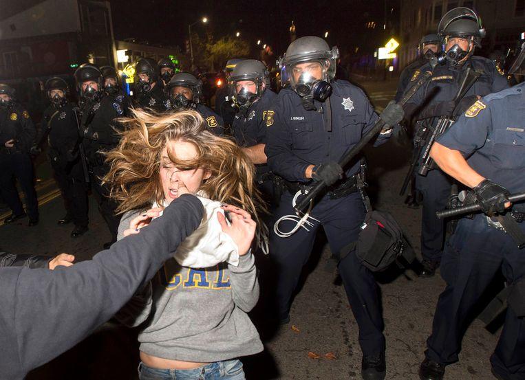 Een demonstrant loopt weg van de politieagenten tijdens een demonstratie in Berkeley, in Californië. Beeld REUTERS